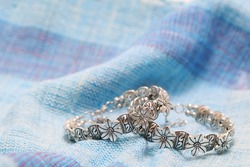 Close up photography of 2 pieces silver bangle soft focus on cotton cloth