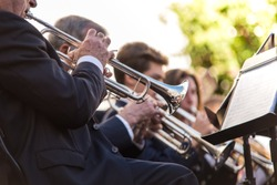 Close up photography of trumpets playing in a music concert. Music sheet on the first plane and wind instruments of several musician in the background.