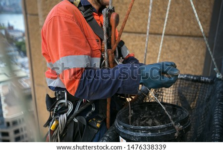 Close up pic of abseiler working at height abseiling twin nylon low stretch static rope wearing safety yellow helmet fall protection PPE harness using blue heavy duty glove conduct concrete repair