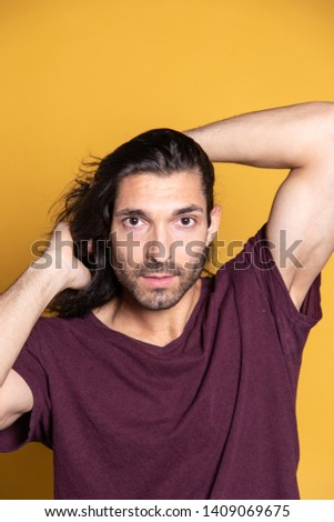 Close up pic of an attractive caucasian young man with long hair on yellow background with natural shadow. Studio session