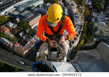 Close up pic of male rope access jobs  worker wearing yellow hard hat, long sleeve shirt, safety harness, working, at height abseiling down from the high rise building site, Sydney city, Australia