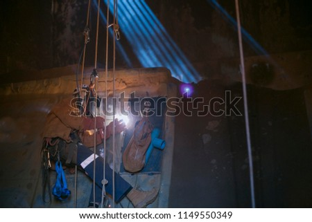 Close up pic rope access welder wearing safety equipment abseiling hanging on harness as fall arrest position welding repairs, maintenance in confined space area on construction site Perth, Australia