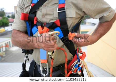 Close up pics of male industrial rope access worker wearing dressing fall arrest safety protection harness and clipping Karabiner into side safety harness loop prior work, construction building site