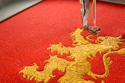 Close up picture embroidery design gold lion on red fabric embroider by machine, copy space on the left side.