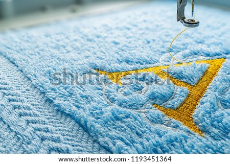 Close up picture embroidery design yellow alphabet monogram A on blue towel embroider by machine, copy space on the left side.