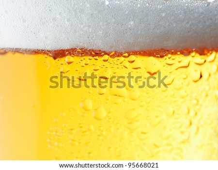 Close up picture of a beer with white foam.