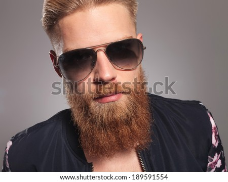 close up picture of a casual young man with a long red beard, looking into the camera. on gray studio background