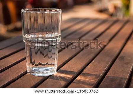 Close-up picture of a glass of water which is half-full standing on a brown wooden table and as the sun shines through the glass the reflection can be seen on the table