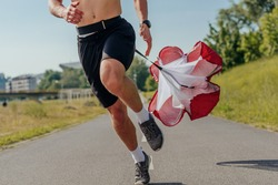Close up picture of a handsome sportsman running with resistance parachute tied to his waist