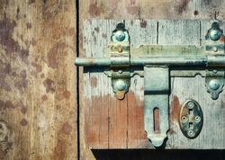 Close up picture of a hasp on a wooden door.