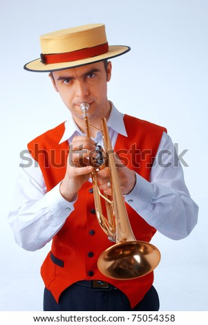 Close up picture of a man in yellow hat and red waistcoat playing on trumpet