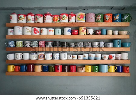 close up picture of a shelf for a cafe or coffee shop decorated by colorful glasses #651355621
