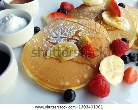 Close-up picture of a sweet breakfast composed of pancakes, fresh berries and fruits, ricotta cheese, jam and honey. Delicious start of a day.