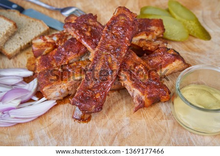 Close up Picture of american style bbq grilled pork spare ribs marinated in honey and served on wooden plate with slices of rustic bread, pickled cucumbers, chopped onions and french style hot mustard