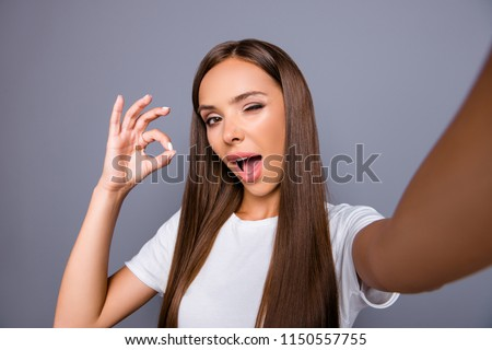 Close up picture of attractive brunette woman wink with open mouth shooting selfie, gesturing ok sign with fingers, having video call, standing isolated on gray background