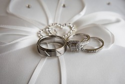 Close up picture of beautiful new pair of platinum wedding rings and white gold engagement ring with big square cut diamond and many small diamonds, white silk ring pillow with white ribbons