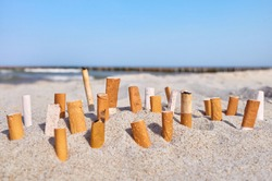 Close up picture of cigarette butts stuck in sand on a beach, selective focus.