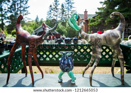 Close-up picture of 2 clay deers or elks, facing each others - Pictures outside at a creative pottery exhibition, on a beautiful summer day