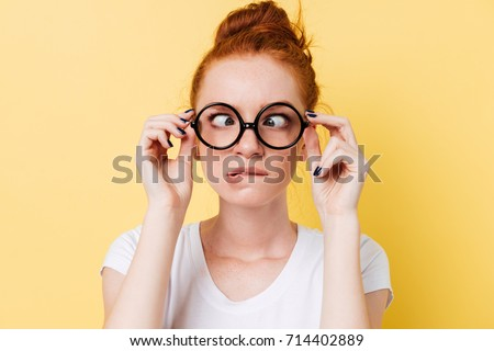 Close up picture of funny ginger woman in eyeglasess showing grimace over yellow background
