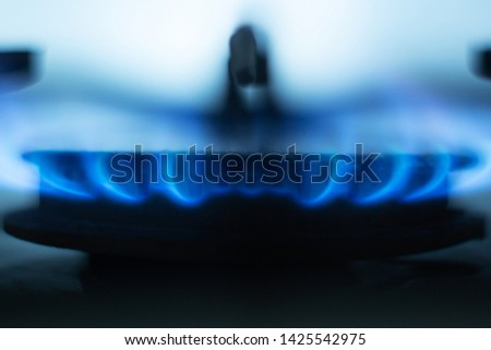 Close up picture of gas hob burning, bright blue flames situated around metallic special round in gas cooker, having light blue background, fire burning at minimum equally. Economy of gas concept.