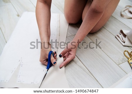 Close-up picture of hands with scissors with blue handles. Young woman, cutting paper pattern with light beige fabric. Cutting process. Sewing tutorial. Pattern making workshop by fashion designer