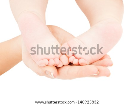close up picture of mother's hand holding baby feet