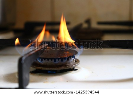 Close-up picture of old and dirty black gas stove burner with blue and orange flames burning for cooking.
