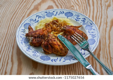 Close up Picture of old rustic plate with roasted spicy chicken wings, mashed potatoes with glazed, baked or fried onions and stainless steel fork, knife on wooden table.