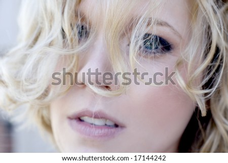 Close-up picture of pretty female with her hair partially covering her face - stock photo