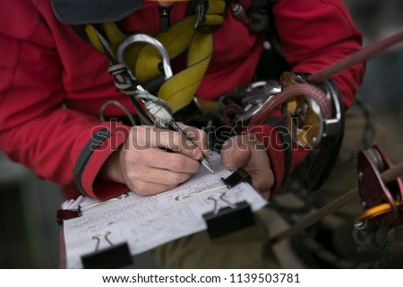 Close up picture of rope access technician engineer worker writing a report of building structure leak, hiatus at hight rise construction building site Sydney, city skyline, Australia