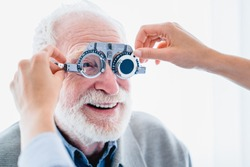 Close up picture of senior male patient with cheerful smile during ophthalmic vision check up