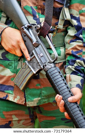 Close-up picture of soldier carrying  M 16  in combat training.