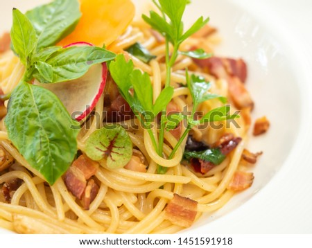 Close up picture of spaghetti bacon fried with dry chilli in white ceramic placte. Ready to serve.