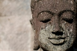 Close up picture of the head of a small stone Buddha statue located in Ubud, Bali - Indonesia