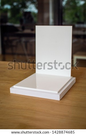 Close up picture of white product pedestal on a wooden table. Shalow depth of field, blurred background. White steps, white back plate for displaying products. #1428874685