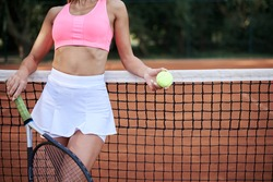 Close-up picture of woman's body, wearing white skirt and pink top,holding tennis racket and light green ball, leaning on tennis net on court with orange ground. Active healthy lifestyle concept
