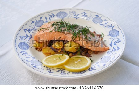 Close up picture on salmon fillet served with roasted potatoes and onion, slices of fresh lemon and chopped fresh dill on the rustic plate. Fresh, healthy, light, diet fish dish for lunch or dinner.