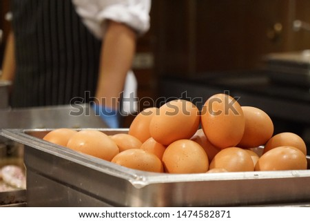 Close-up pictures of chicken eggs in a rectangular stainless steel container with a back blurred image of the chef who is cooking.