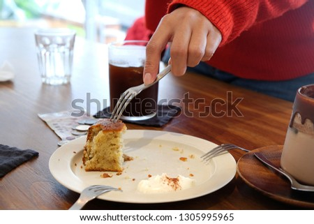 Close-up pictures of hands scooping banana cakes to eat with a fork. Coupled with drinking coffee on a wooden table in a coffee shop