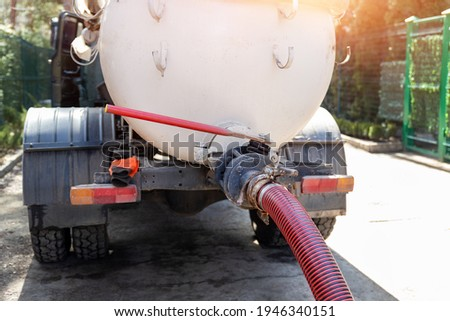 Close-up pipe hose of sewage truck car engine emptying home sewerage tank. Septic cleaning vacuum service and maintenance suburban countryside home. Suction vehicle cleaner machine pumping drainage Foto stock ©