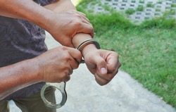 Close up plainclothes policeman's hands handcuffing young villain man with blurred outdoor background in afternoon, high angle view with space