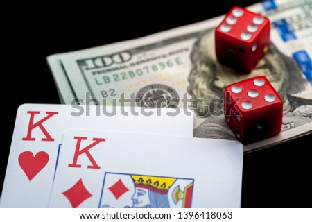 Close-up - playing cards, red gaming dices and Stack of american dollars on black table. Casino, gambling game chance concept #1396418063