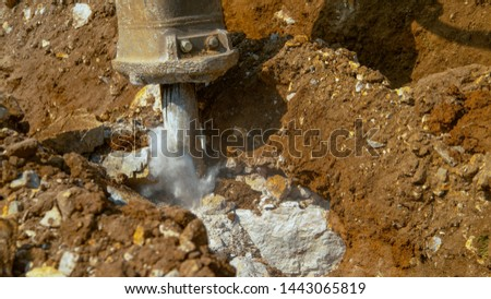 CLOSE UP: Pneumatic jackhammer creates a cloud of grey dust as it strikes against solid rock sitting deep in the brown soil at a busy construction site. Heavyweight drill crushing stones and dirt.