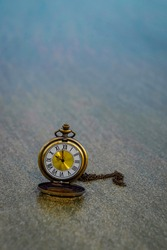 close up pocket watch on sand with nature copy space background, saving and manage time to success business, travel bubble and relaxation lifestyle concept