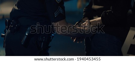 CLOSE UP Police officer handcuffs a suspect near police car, African-American Black criminal. Lights flashing in the background. Shot with anamorphic lens Stock photo ©