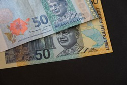 Close up Polymer Money RM50 In conjunction with the XVI Commonwealth Games in Kuala Lumpur, Malaysia and RM50 banknotes on black background.