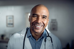 Close-up portait of happy black doctor working at medical clinic and looking at camera.