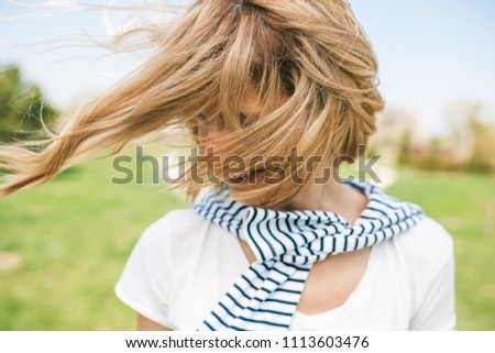Close up portait of romantic happy female with blond blowing hair enjoy weather and sunny day outside. Portrait of beautiful young woman smiling with windy hair on face in the park. People, lifestyle