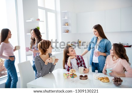 Close up portrait amazing beautiful she her ladies family meeting sister cousins nephews stand sit round big white table in bright kitchen hold cups girls day night holiday indoors #1309130221