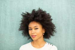 Close up portrait beautiful young african american woman with afro hair against green background